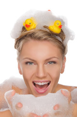 beautiful young woman with soapy foam and ducks