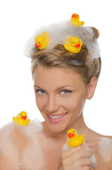 smiling young woman with ducks and soap foam
