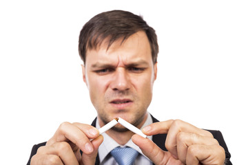Young businessman breaking a cigarette, concept for give up smok