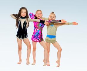 Three cheerful girl gymnasts.