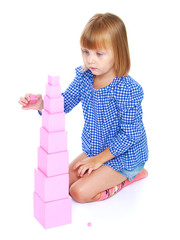 Little girl sitting on his lap builds high pink tower, Montessor