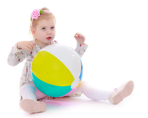 Little girl sitting on the floor with a large inflatable ball.