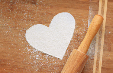 heart from white flour on wooden background and rolling-pin