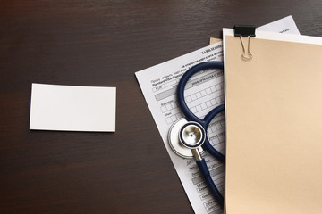 A blank, a medical record form with a  stethoscope on a wooden