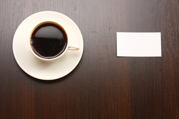 A cup of coffee and a note card from a wooden desk from above