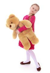 Little girl holding a teddy bear. Portrait in full growth.