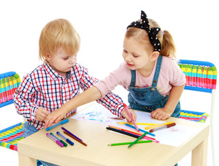 Boy and girl drawing with pencils sitting at the table.