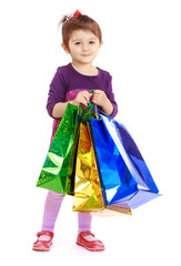 Little girl goes shopping with large colored blocks.