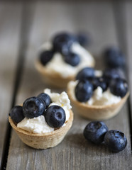 Blueberry tartlets on rustic wooden kitchen background
