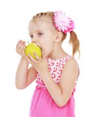 little girl chews big green apple.