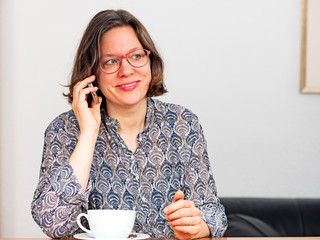 Frau mit Cappuccinotasse telefoniert