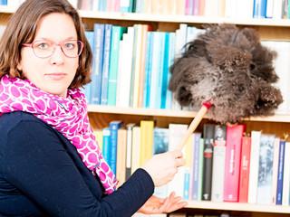 Frau staubt Bücherregal ab