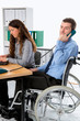 man in wheelchair and his  is female colleague working in the jo