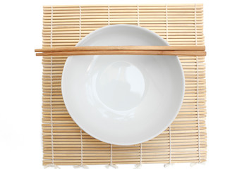 Bowl white empty and chopstick on mat
