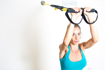 Athletic woman makes TRX exercise