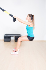 Sporty woman makes suspension training