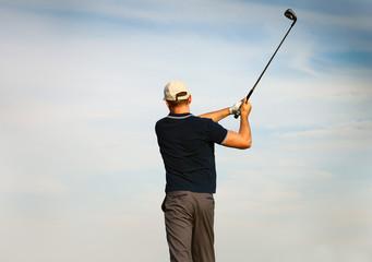 Athletic young man playing golf, golfer hitting fairway shot