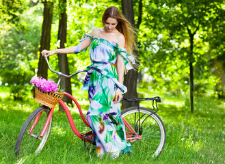 Beautiful blond woman wearing a nice dress having fun in park wi