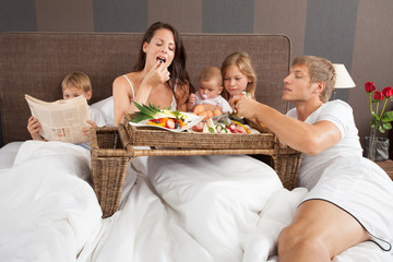 Family breakfast in bed - boy reading newspaper