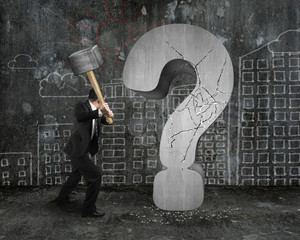 businessman holding hammer cracked question mark with city build