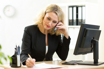 Businesswoman working in office. Employee talking by phone and