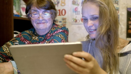 Young and senior woman looking through photos on pad
