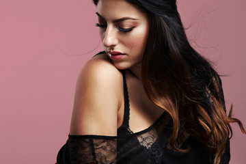 sensual plus size model on a pink background with a blowing hair