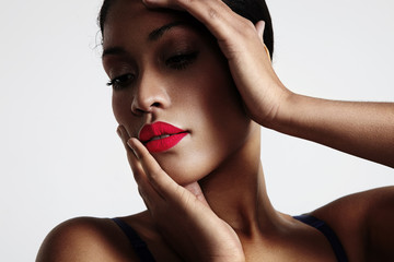 woman with a bright lips and hands touching her face