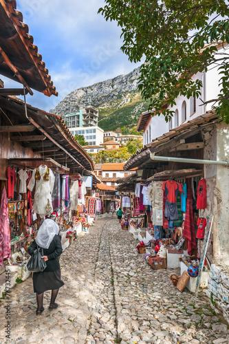 Elderly woman walking along the bazaar ok Kruja - 76732445