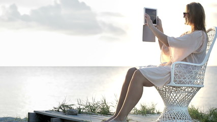 Woman near the sea making photos using pad