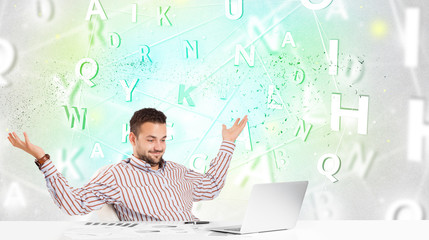 Business man at desk with green word cloud