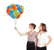 Young women holding colorful balloons