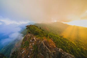 Shining light through a dark sky over mountain