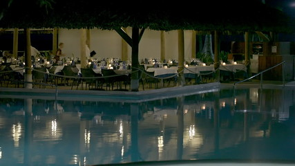 Restaurant by swimming pool on resort in the evening