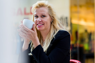 Frau beim Kaffeetrinken draußen im Stadt Cafe