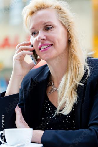 canvas print picture Frau mit Handy im Cafe beim Kaffee trinken