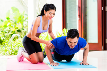 Asian woman helping man with push-up
