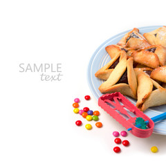 Hamantaschen cookies on plate and grogger on white background