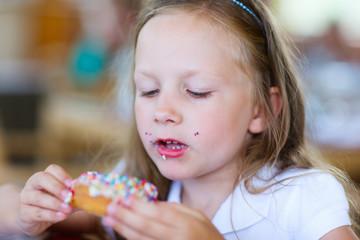 Little girl eating donut