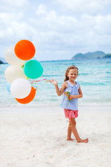 Little girl with balloons at beach