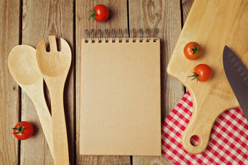 Cardboard notepad with kitchen utensils on wooden table