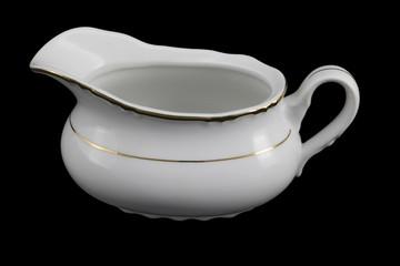 Porcelain sauce-boat on a black background