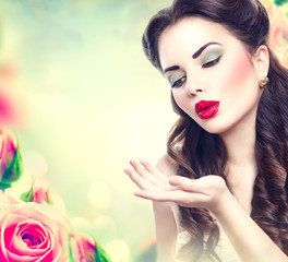 Retro woman portrait in pink roses garden. Vintage styled girl
