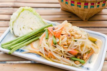 Closeup spicy green papaya salad. Traditional Lao and Thai dish.