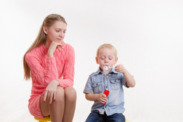 Mom watches her son to blow bubbles