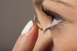 A woman putting on contact lenses - 76743289