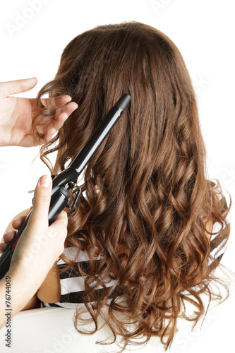 Poster, Tablou Stylist using curling iron for hair curls, close-up, isolated