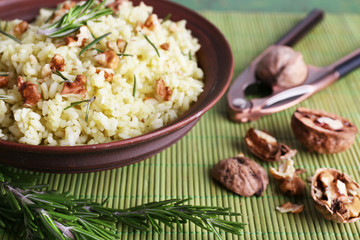 Rice with walnuts and rosemary in plate on bamboo mat