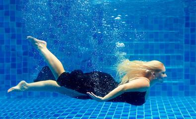 beautiful plus size woman diving in pool