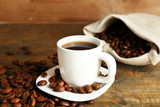 Fototapety Cup of coffee with beans on rustic wooden background